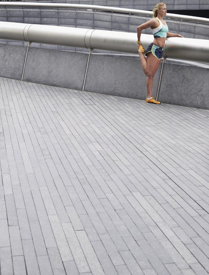 Kvinnlig idrottsman nen Stretching Outdoors arkivfoton