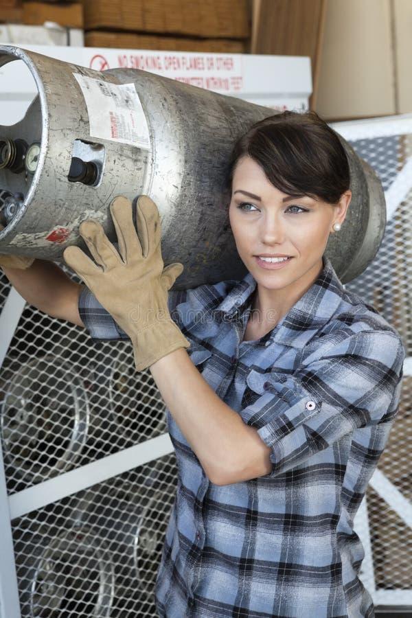 Kvinnlig industriarbetare som bär en propancylinder arkivbilder