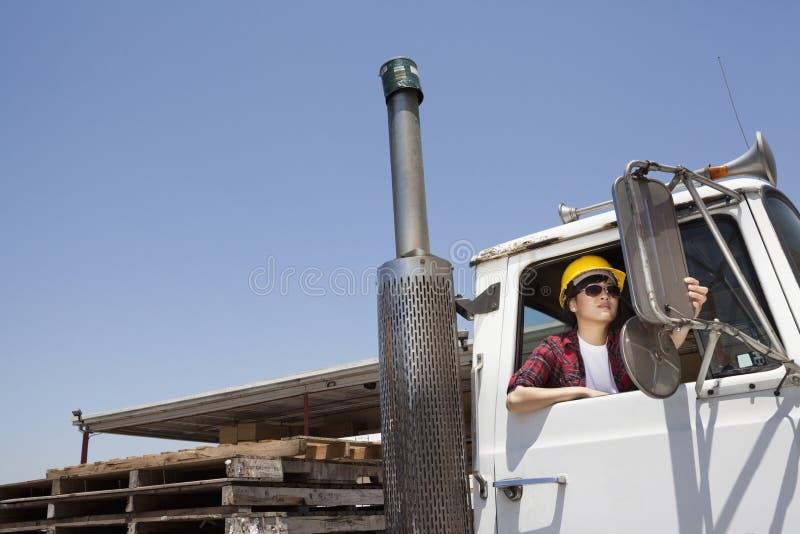 Kvinnlig industriarbetare som justerar spegeln, medan sitta, i att logga lastbilen royaltyfri foto