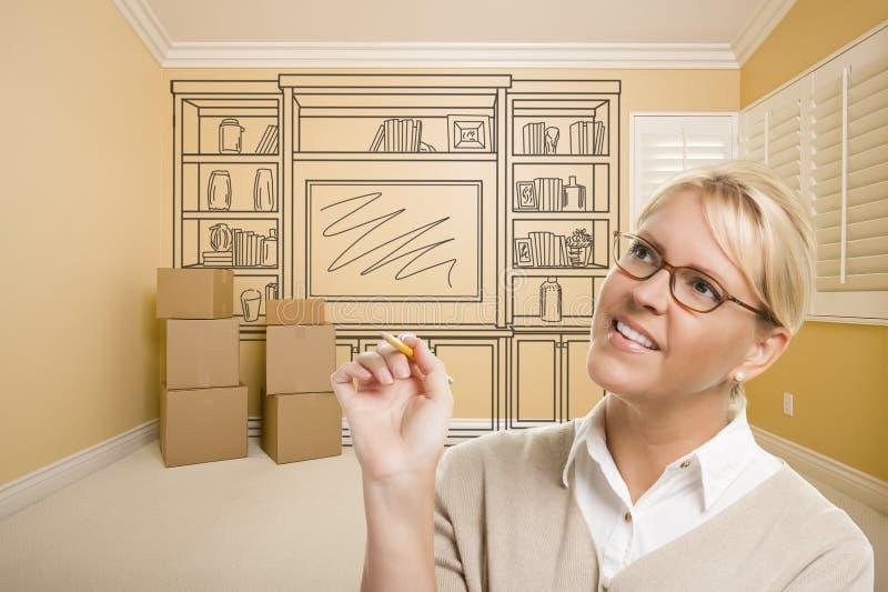 Kvinnlig innehavblyertspenna i rum med teckningen av underhållningenheten royaltyfri bild