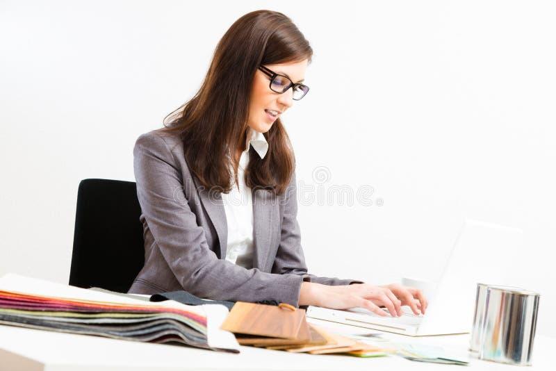 Kvinnlig inreformgivare At Her Desk fotografering för bildbyråer