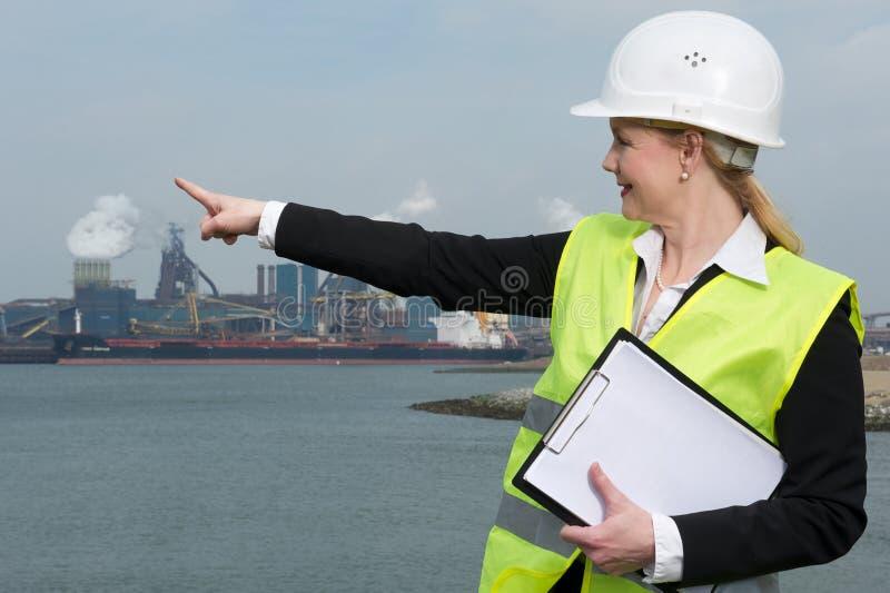 Kvinnlig inspektör i hardhat och säkerhetsväst som pekar på den industriella platsen arkivbild