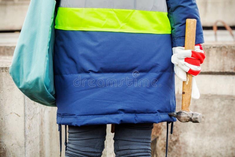 Kvinnlig inspektör med hammaren nära konkreta kvarter royaltyfri fotografi