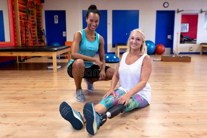 Kvinnlig instruktör och kvinna för handikappade personer som aktiv hög ser kameran i sportmitt royaltyfri bild