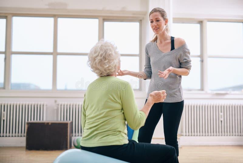 Kvinnlig instruktör som diskuterar framsteg med den äldre kvinnan arkivfoto