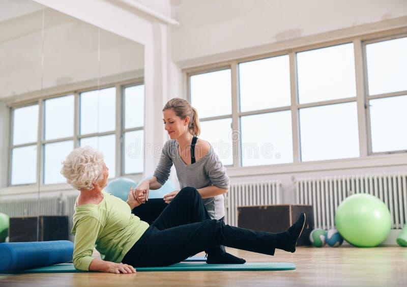 Kvinnlig instruktör som hjälper den gamla kvinnan som får upp på idrottshallen royaltyfri foto