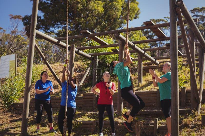 Kvinnlig instruktör som instruerar kvinnor att klättra ett rep i kängalägret arkivbilder