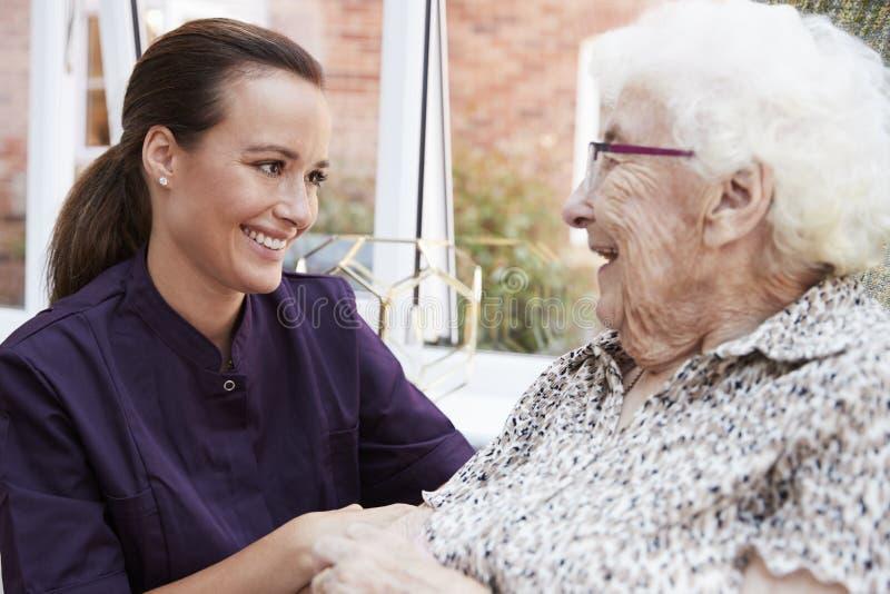 Kvinnlig invånare som sitter i stol och talar med vårdare i avgånghem arkivbild
