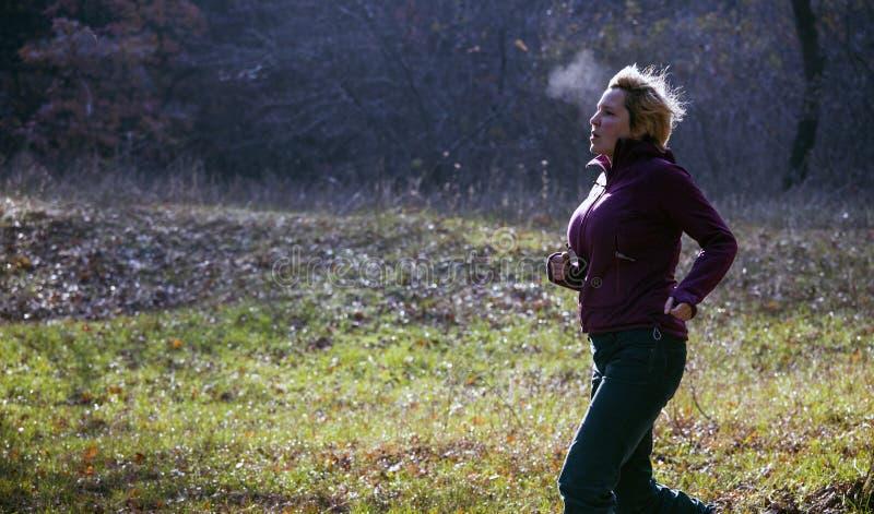 Kvinnlig joggerspring på den kalla dunsten för morgonresningandedräkt fotografering för bildbyråer