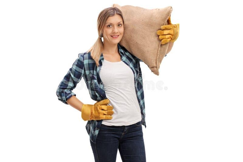Kvinnlig jordbruks- arbetare som bär en säckvävsäck arkivbild