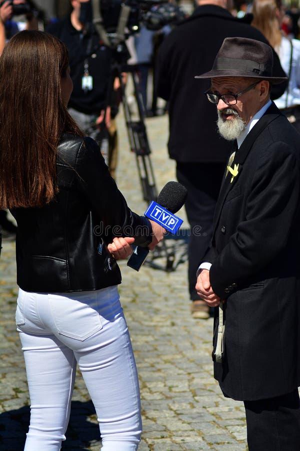 Kvinnlig journalist TVP med att intervjua f?r mikrofon royaltyfri bild