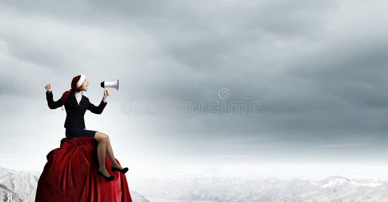Kvinnlig jultomten med megafonen royaltyfria bilder