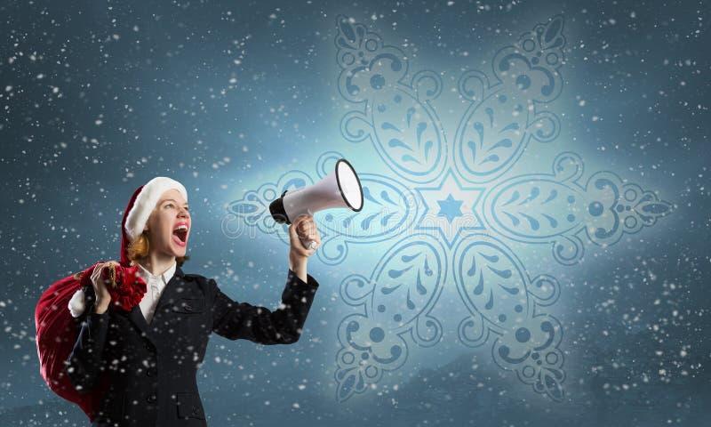 Kvinnlig jultomten med megafonen royaltyfri foto