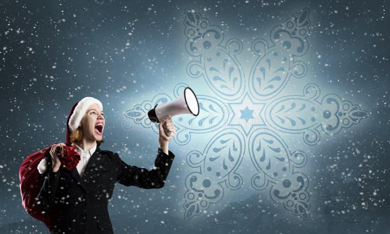 Kvinnlig jultomten med megafonen arkivbild