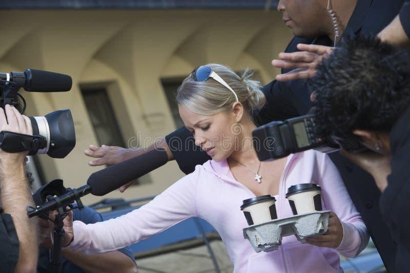 Kvinnlig kändis och Paparazzi fotografering för bildbyråer