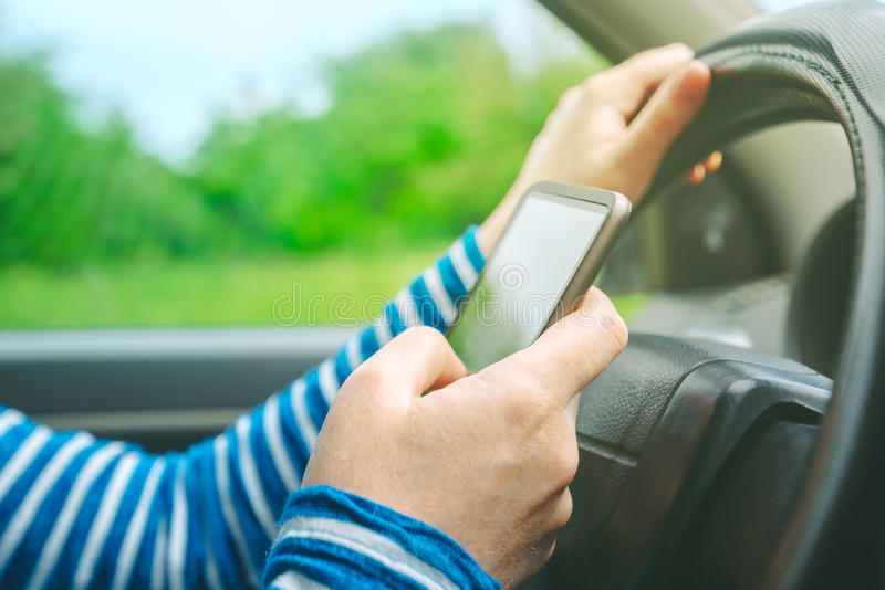 Kvinnlig körande bil och smsande smsmeddelande på smartphonen fotografering för bildbyråer