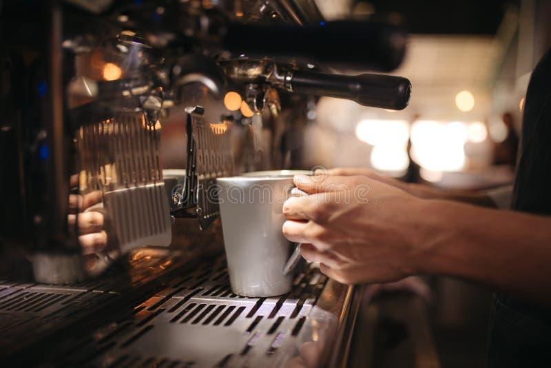 Kvinnlig kaféarbetare som förbereder kaffe i maskin arkivfoto