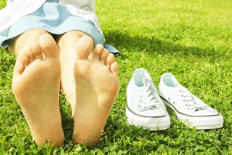 Kvinnlig kal fot på mawed gräsmattagräs Den unga kvinnan som utomhus barfota vilar, tar ett avbrottsbegrepp Student på högskolaun arkivfoton