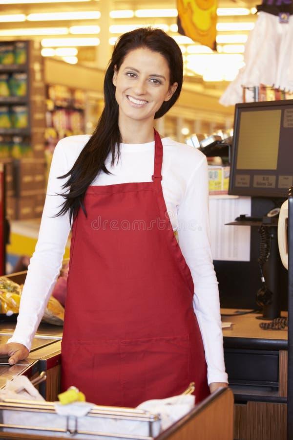 Kvinnlig kassörska At Supermarket Checkout arkivfoton