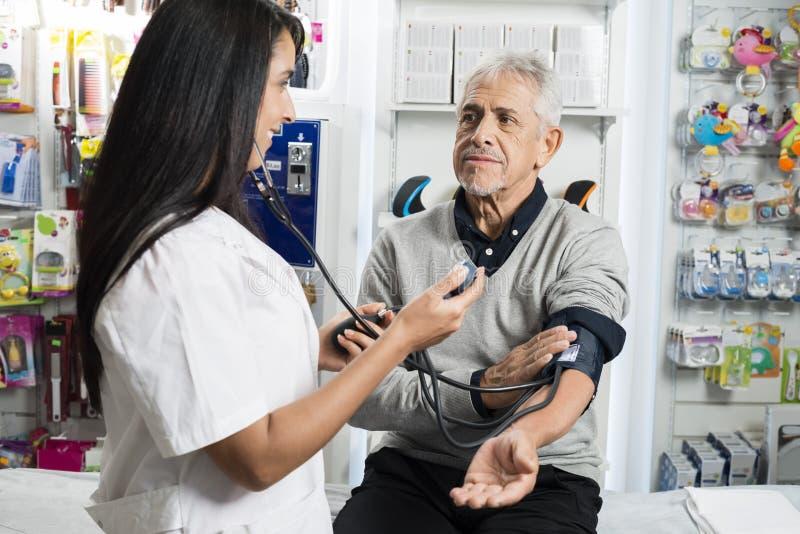 Kvinnlig kemist Checking Blood Pressure av den höga mannen royaltyfria foton