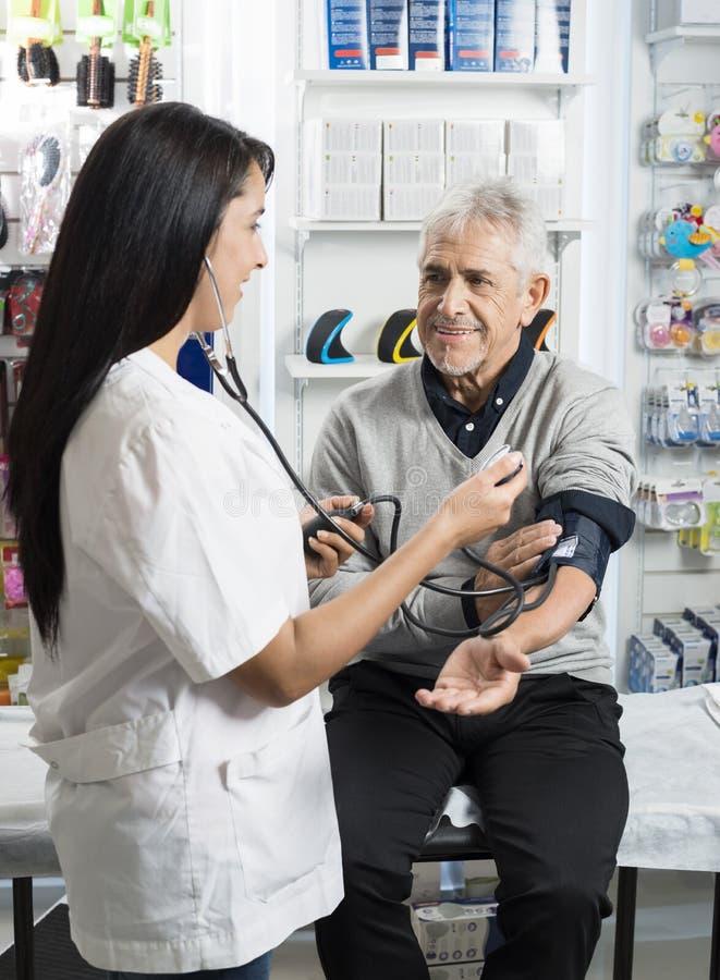 Kvinnlig kemist Checking Blood Pressure av den höga patienten arkivbild