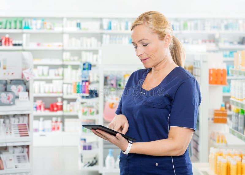 Kvinnlig kemist Using Digital Tablet i apotek royaltyfri foto