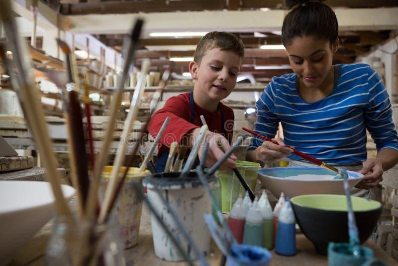 Kvinnlig keramiker- och pojkemålningbunke arkivfoto