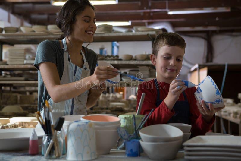 Kvinnlig keramiker- och pojkemålningbunke arkivfoton