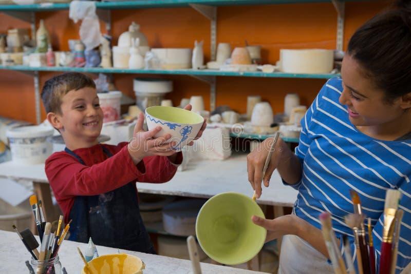 Kvinnlig keramiker- och pojkemålningbunke arkivbild
