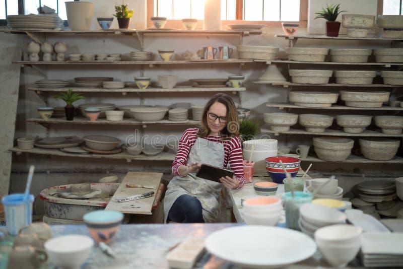 Kvinnlig keramiker som använder den digitala minnestavlan royaltyfria foton