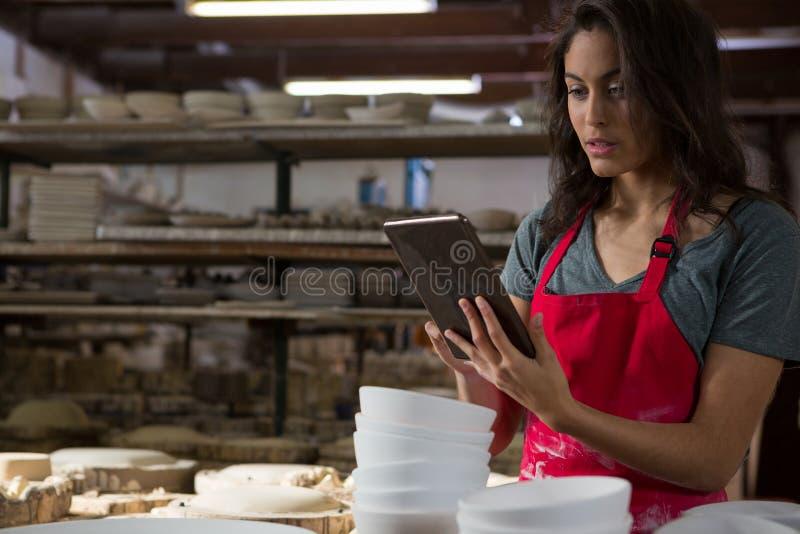 Kvinnlig keramiker som använder den digitala minnestavlan arkivbilder