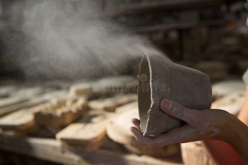 Kvinnlig keramiker som blåser damm från gyttja arkivbild
