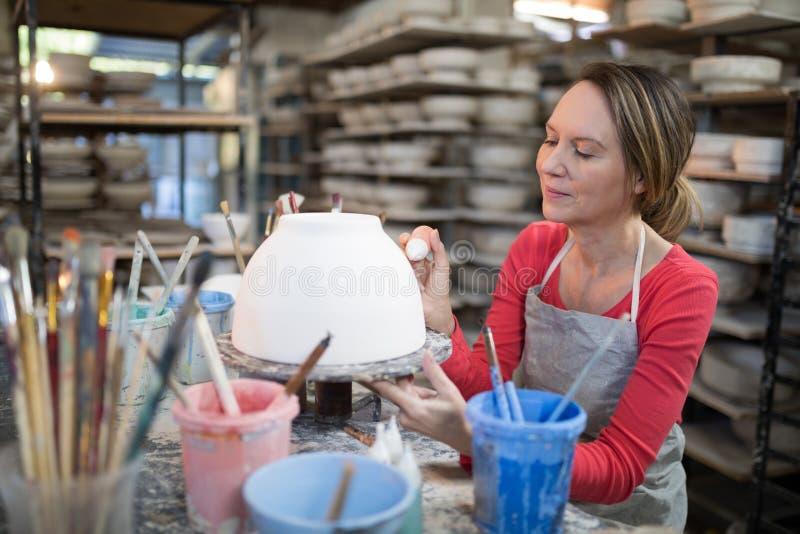 Kvinnlig keramiker som dekorerar bunken arkivfoto