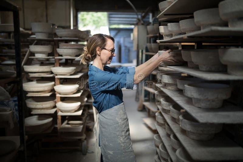 Kvinnlig keramiker som förlägger bunken i hylla arkivfoto