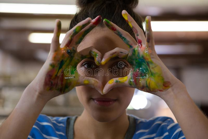 Kvinnlig keramiker som gör en gest med målade händer arkivbild