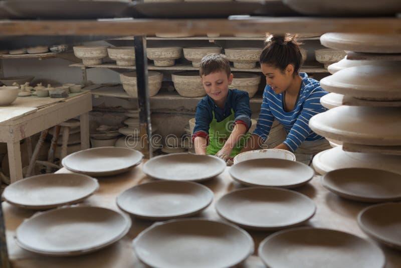 Kvinnlig keramiker som hjälper en pojke arkivbild