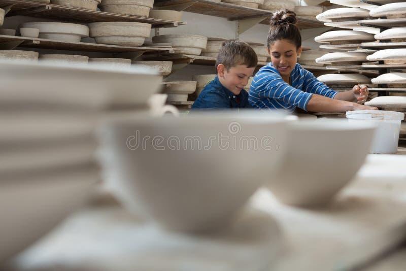 Kvinnlig keramiker som hjälper en pojke royaltyfri bild