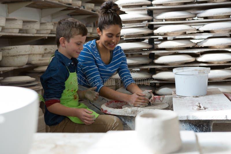 Kvinnlig keramiker som hjälper en pojke royaltyfri foto