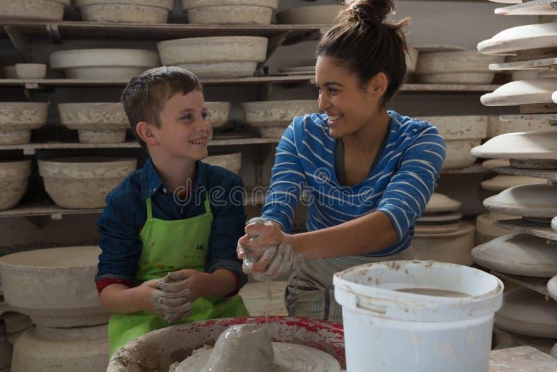Kvinnlig keramiker som hjälper en pojke fotografering för bildbyråer
