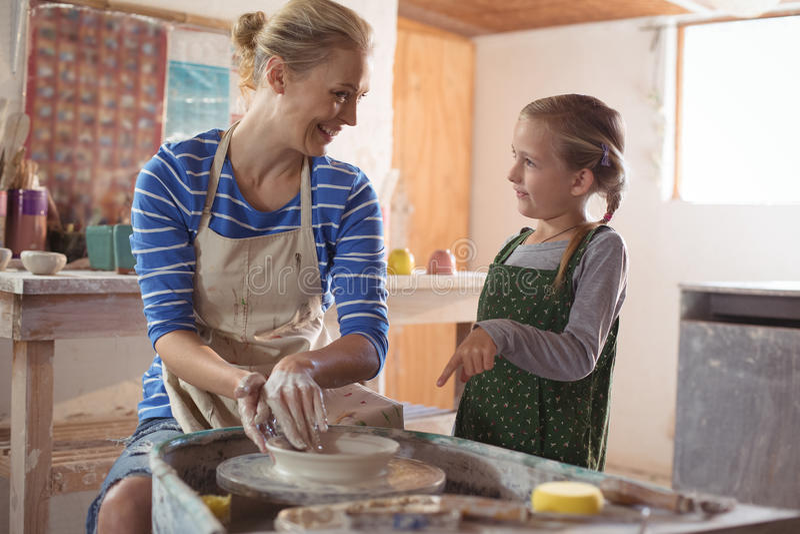 Kvinnlig keramiker som hjälper flickan royaltyfri foto