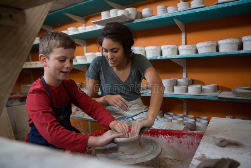 Kvinnlig keramiker som hjälper pojken, i att gjuta en lera arkivbild