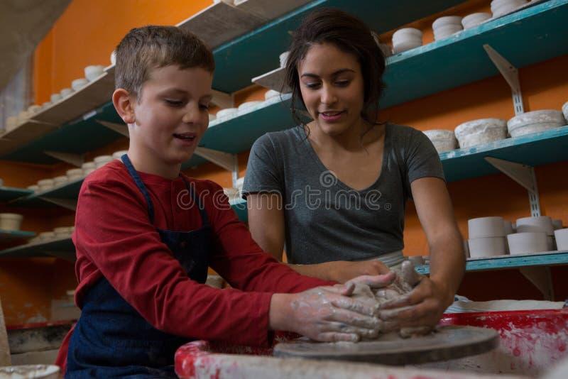 Kvinnlig keramiker som hjälper pojken, i att gjuta en lera fotografering för bildbyråer