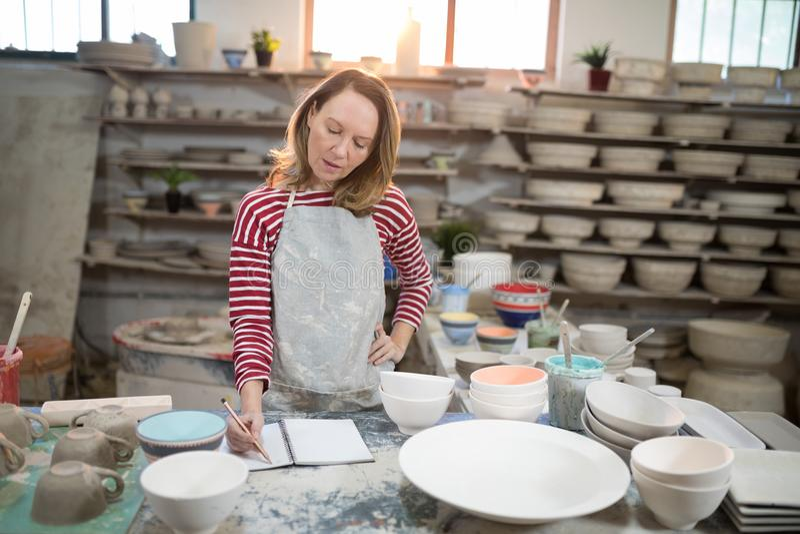 Kvinnlig keramiker som kontrollerar beställningarna i anteckningsbok royaltyfri foto