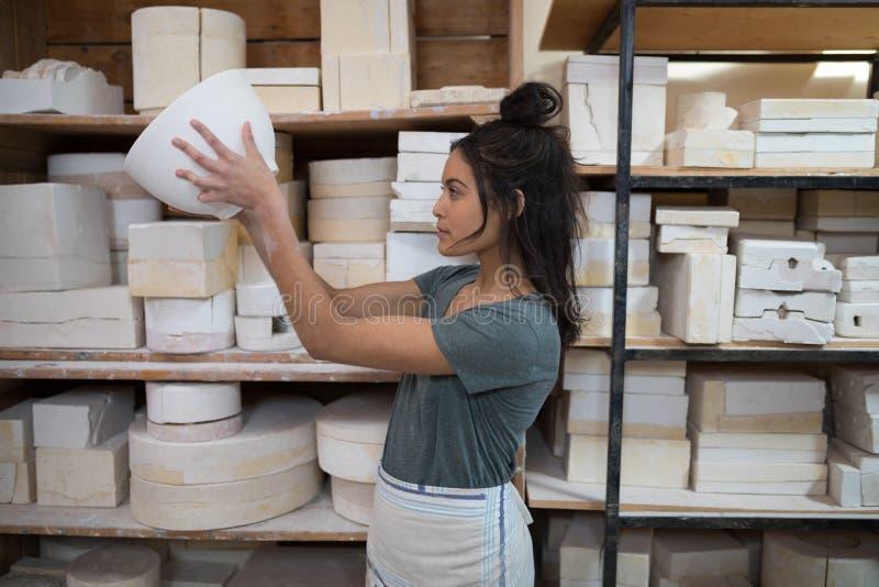 Kvinnlig keramiker som kontrollerar bunken royaltyfria bilder