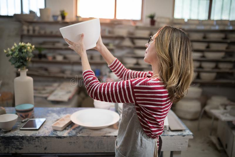 Kvinnlig keramiker som kontrollerar bunken royaltyfri fotografi