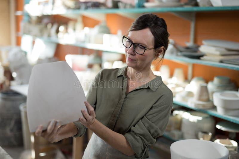 Kvinnlig keramiker som kontrollerar den keramiska vasen arkivfoto