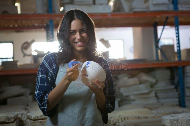 Kvinnlig keramiker som målar en bunke royaltyfri fotografi