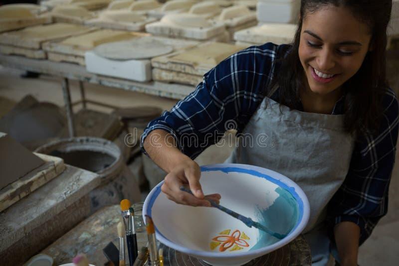 Kvinnlig keramiker som målar en bunke royaltyfri bild