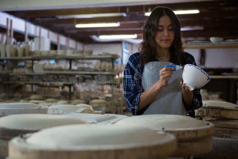 Kvinnlig keramiker som målar en bunke arkivfoton