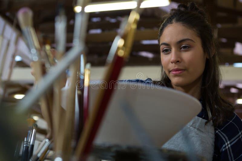 Kvinnlig keramiker som målar en bunke arkivbild